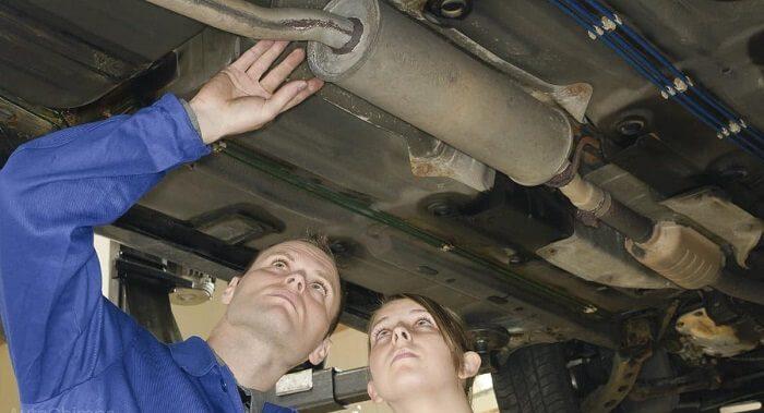 car-mechanics-looking-at-car-muffler-or-exhaust-system
